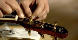 holding the guitar strings to guide when winding